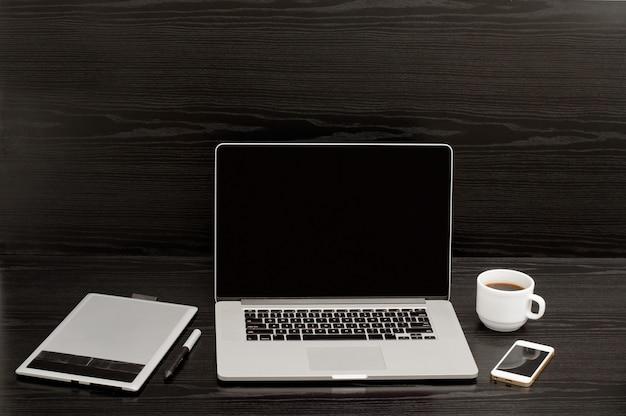 Откройте ноутбук, кружку кофе, телефон и графический планшет на черном фоне