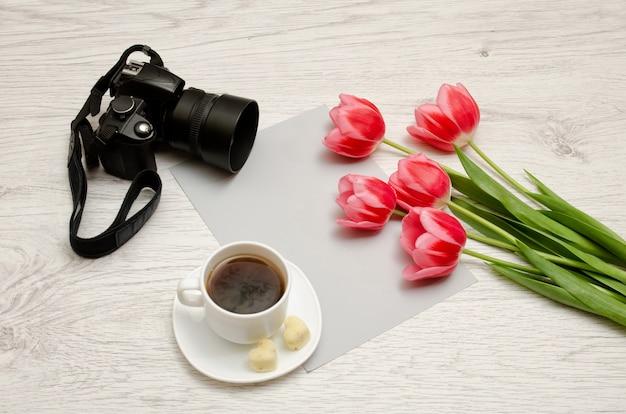 紙の空白のシート、紅茶とカメラのマグカップ、明るい木製の背景にピンクのチューリップ。