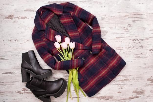 暖かい市松模様のコート、黒い靴、チューリップ。