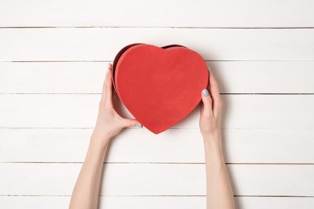Женские руки держат красную коробку в форме сердца в деревянном столе