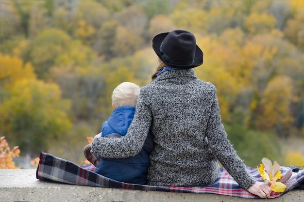 Мать и сын сидят на возвышенности. осень. лес на расстоянии. вид сзади