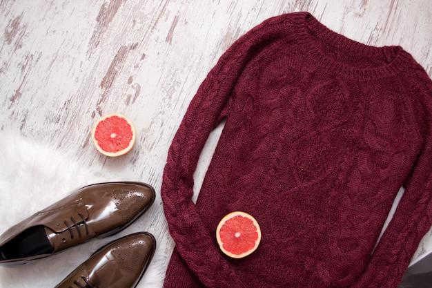 マルーンニットセーター、茶色のパテントレザーの靴、カットグレープフルーツの半分。