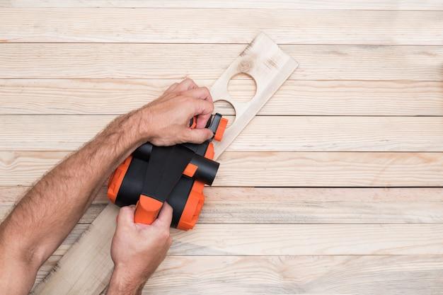 Электрический рубанок в мужской руке