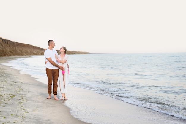若い夫婦が海の海岸に沿って歩く