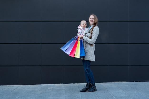 小さな娘と買い物袋を持つ若い母親
