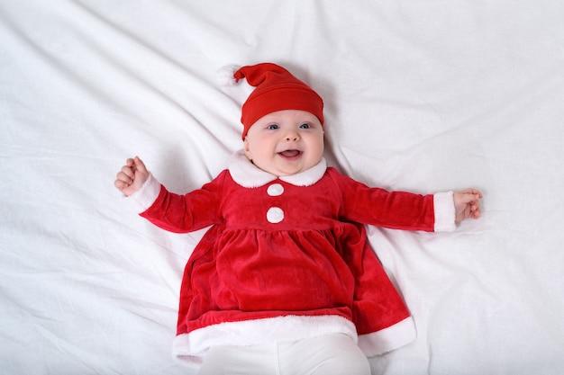 サンタの帽子と赤いドレスの少女の笑顔のポートレート。空白の上に横たわる。クリスマスのコンセプト
