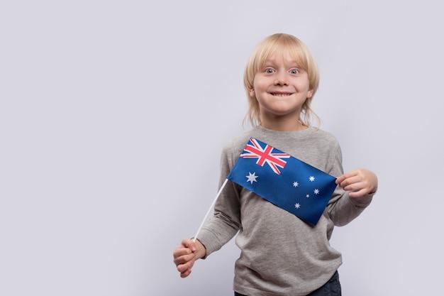 ホワイトスペースに手でオーストラリアの旗を持つ陽気な金髪の少年のポートレート