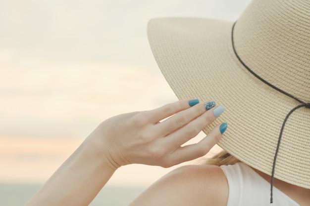 帽子と女性の手の一部をクローズアップ。宇宙の夕焼け空