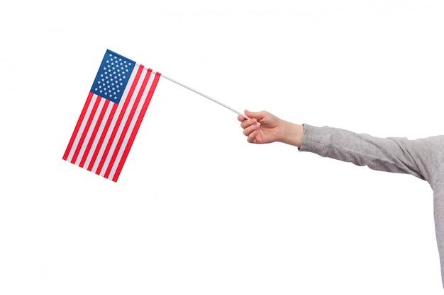 Детская рука держит флаг сша, изолированных на пустое пространство. флаг соединенных штатов америки