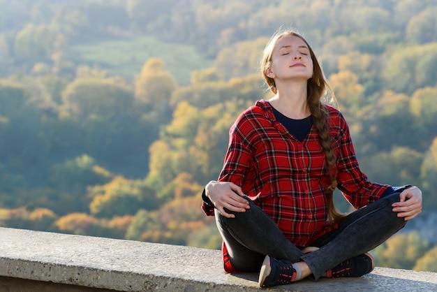 妊娠中の女性は目を閉じて丘の上に座っています。瞑想。スペースの秋の森