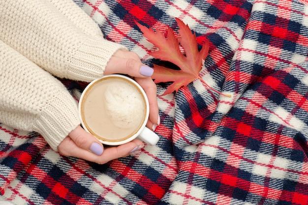 女性の手、市松格子縞、秋の葉のカプチーノ。ファッショナブルなコンセプト