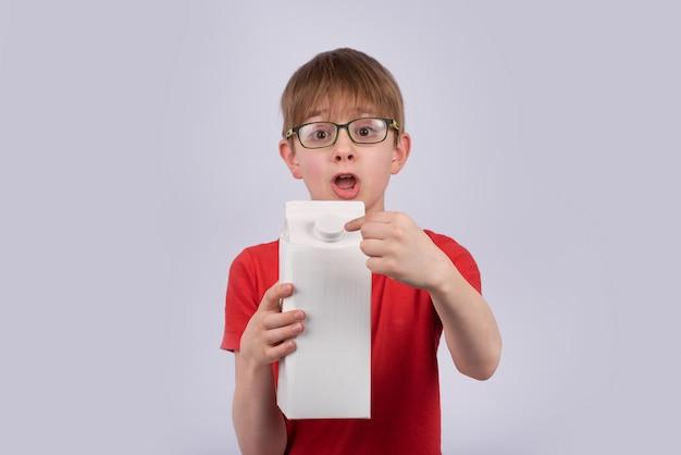 カートンボックスを保持しているメガネで驚いた少年