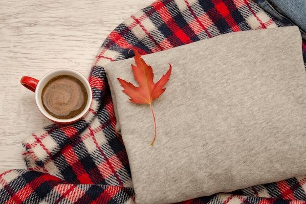 グレーのセーター、格子縞、コーヒーマグ。紅葉。ファッショナブルなコンセプト