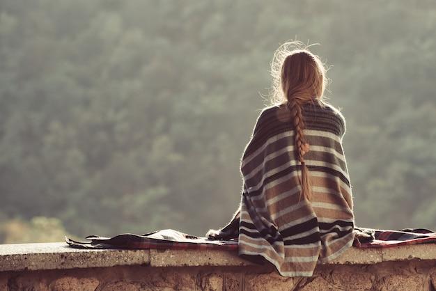 丘の上に座って自然を楽しんでいる若い女性。背面図
