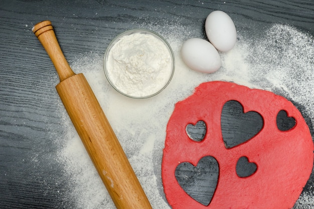 赤いハートは、黒いテーブルの上に麺棒、卵、小麦粉で生地を切り取る