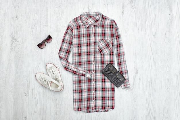 市松模様の女性のシャツ、黒いハンドバッグ、白いスニーカー、サングラス