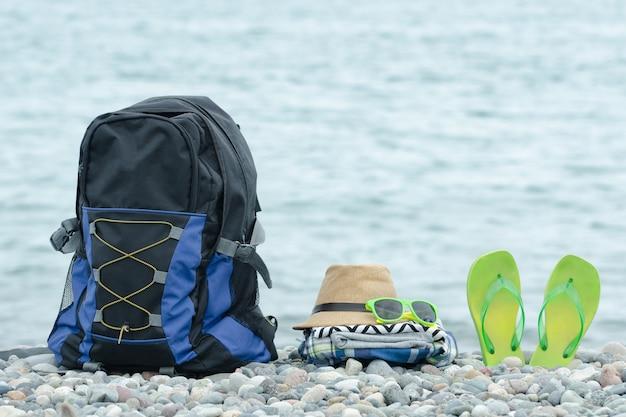 小石のビーチでバックパック、帽子、ビーチサンダル。