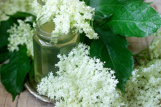Домашний сироп из бузины цветы в стеклянной банке и бузины на деревянном столе деревенском стиле.