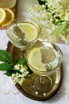 Прохладный напиток с лимоном и бузиной сироп в очках на металлическом подносе. деревенский стиль