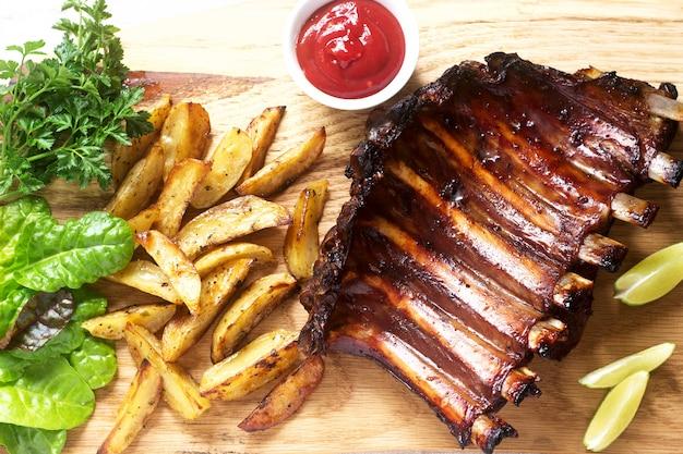 Домашнее запеченное мясо ребра подается с картофелем фри, зеленью, лаймом и кетчупом на деревянной доске. деревенский стиль