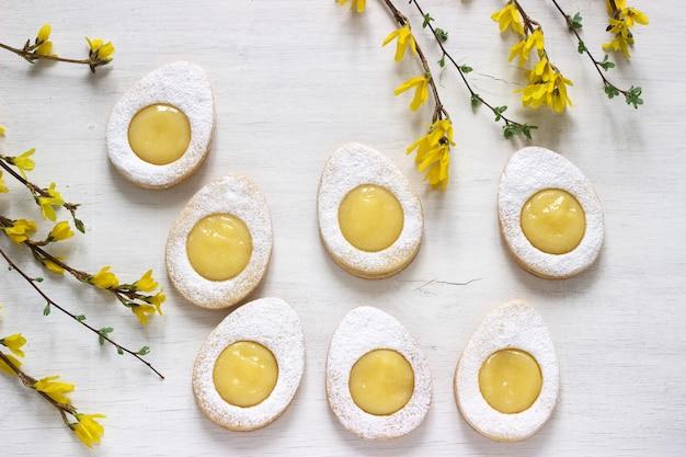 自家製イースターレモンクッキーと明るい背景にレンギョウ咲く小枝。