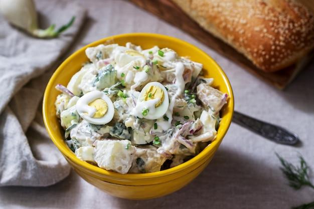 卵とマヨネーズを添えた伝統的なアメリカのポテトサラダにパンを添えて。素朴なスタイル。