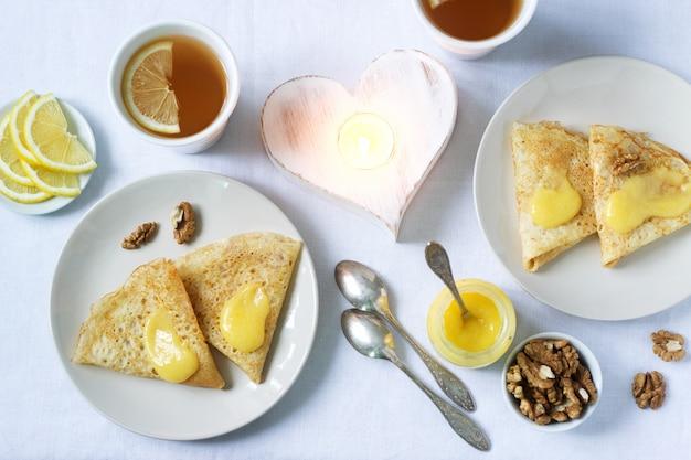 Завтрак на двоих с блинами, лимонным кремом и чаем. завтрак в день святого валентина.