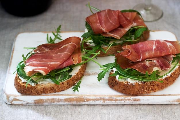 Традиционная итальянская закуска брускетта из поджаренного хлеба с творогом, рукколой и прошутто.