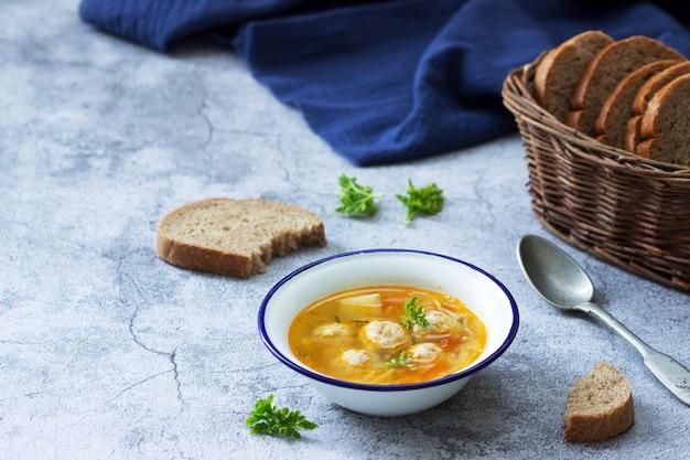 Диетический суп с фрикадельками, картофелем и лапшой, подается с ржаным хлебом с отрубями. детское меню.