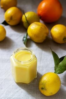 ガラスの瓶に柑橘類の豆腐とリネンのテーブルクロスに柑橘系の果物。素朴なスタイル。
