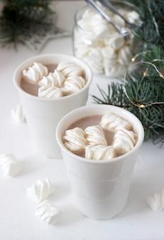 白いカップのマーシュメローとトウヒの枝と花輪の白いテーブルの上のガラスの瓶にマシュマロとココア。