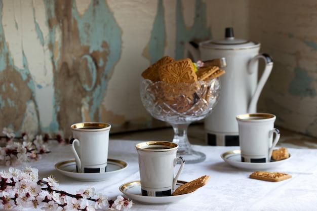 開花枝と古い食器棚の背景にショートブレッドクッキーとお菓子を添えてコーヒー。