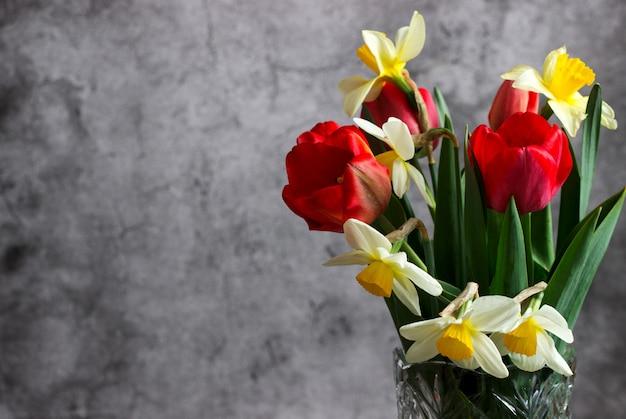 チューリップと水仙のブーケは、コンクリートの壁の背景にクリスタルの花瓶に。