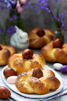 Пасхальные булочки, крашеные яйца и цветы на сером фоне бетона.