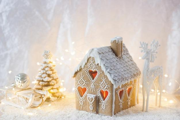 ジンジャーブレッドの家、クリスマスツリー、明るい背景に鹿の姿。ボケ効果。