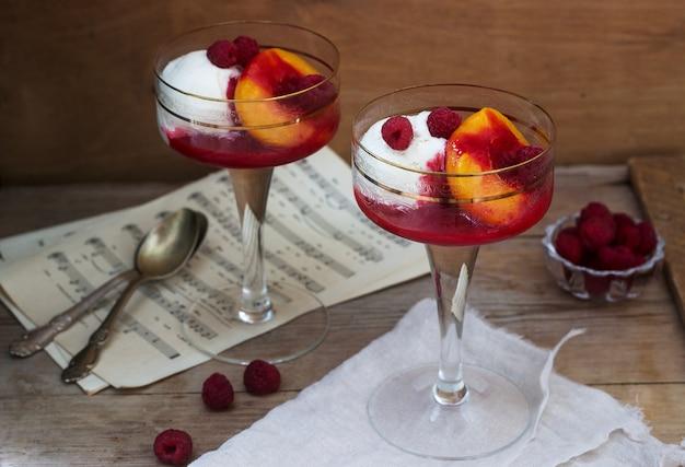 Десерт из мороженого, персика и малины под соусом австралийской оперной певицы мельбы. деревенский стиль