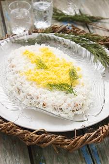 Традиционный домашний салат из мимозы с рыбой, овощами и яйцом. советская жизнь. деревенский стиль, выборочный фокус.