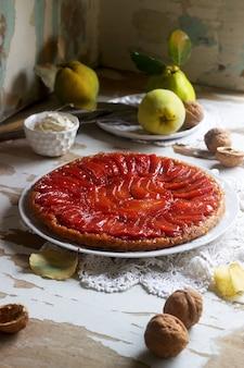 マルメロのタルトタタンは、木製の表面にホイップクリーム、マルメロのフルーツ、クルミを添えて。素朴なスタイル。