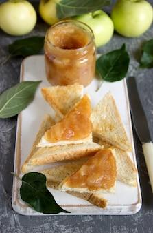 Яблочное варенье в стеклянной банке с хлебом тосты и спелые яблоки на деревянной поверхности. деревенский стиль