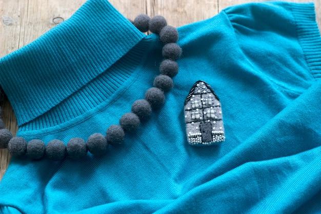 プルオーバーやセーターを背景にしたフェルト製のウールジュエリー。