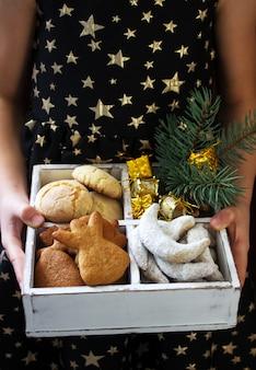 Женщина держит ассорти рождественское печенье и рождественские украшения в деревянной коробке