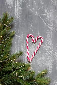 モミの枝、花輪、灰色のコンクリートのキャンディー杖と冬の背景