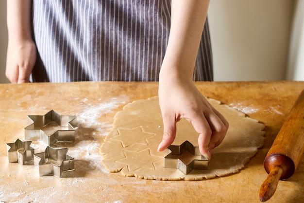 ジンジャービスケットの準備。女性は星形としてクッキーを切り取ります。ペストリー料理、自家製料理のコンセプト。