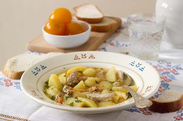 シチュー、ロースト、または肉とジャガイモのスープ、缶詰のトマトとパンを添えて。