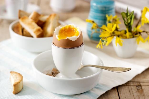 半熟卵、パントースト、クリーム入りコーヒー、新鮮な新聞からの朝食。