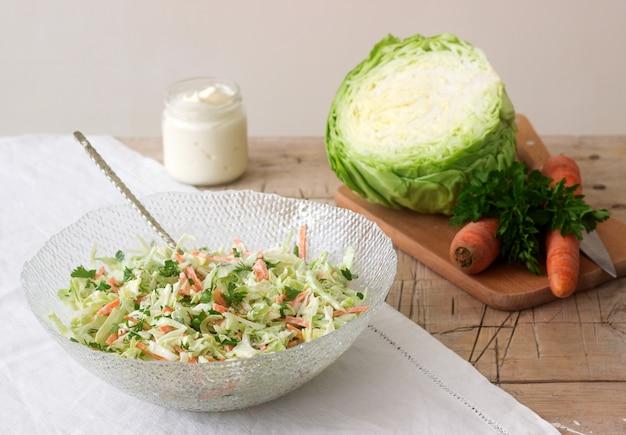 Свежий салат из капусты в миску и ингредиенты для салата. деревенский стиль