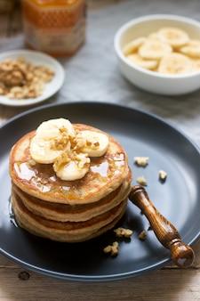 バナナ、ナッツ、蜂蜜入りのパンケーキにお茶を添えて。素朴なスタイル。