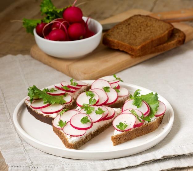 Аппетитные бутерброды из ржаного хлеба с творогом, редисом и салатом. деревенский стиль