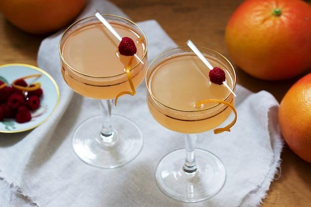 グレープフルーツジュースとシャンパンカクテル、ゼストとラズベリーを添えて。素朴なスタイル。