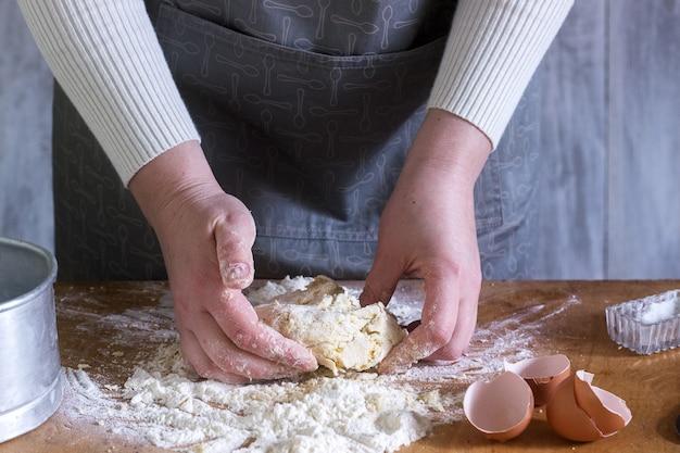 Женщина делает домашнюю лапшу из муки, яиц и соли. деревенский стиль